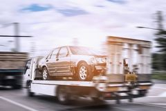 Broken car on tow truck after traffic accident motion blur. Broken car on tow truck after traffic accident, on the road service, motion blur fast move Stock Image