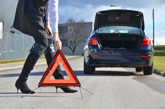 Broken car and triangle. Girl, broken car and triangle Stock Photography
