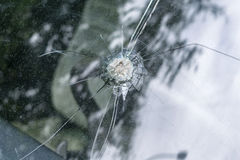 Broken car windshield with radial cracks and a hole in the middle. Royalty Free Stock Photos