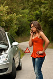 Broken Car - Young Woman Calls for Assistance. A woman calls for assistance using her mobile phone, after her car broke down on the road side Royalty Free Stock Images