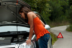Broken Car - Young Woman Waits for Assistance. A woman waits for assistance with her car broke down on the road side, after calling for help Royalty Free Stock Photo