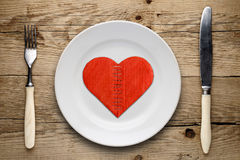 Broken cardboard heart on plate Stock Images