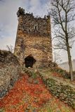 Broken Castle tower. Castle tower by the tree on the hill covered by foliage royalty free stock images