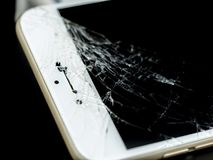 Broken Cell Phone on Black Background. Modern mobile smart phone with broken cracked screen isolated on black background, close up royalty free stock photos