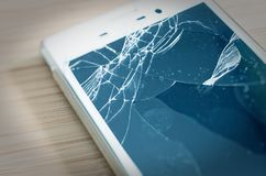 Broken cell phone with display damage and splintered display to symbolize damage to the phone display.  stock photos
