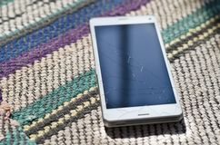 Broken cell phone glass screen on the ground floor. Broken cell phone glass screen on the ground stock photos