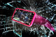 Broken Cell Phone. Broken cell phone going through shards of glass royalty free stock photos