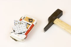 Broken cell phone and hammer. In a white background Royalty Free Stock Photo