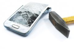 Broken cell phone with a hammer on a white background. Broken stock photography
