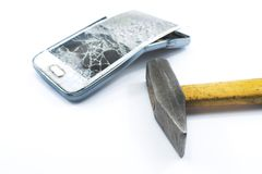Broken cell phone with a hammer on a white background. Broken stock photos