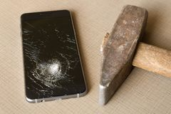 A broken cell phone and hammer on grey background royalty free stock photo