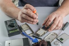 Broken cell phone repair. Smartphone parts and tools for recovery, selective focus royalty free stock photo