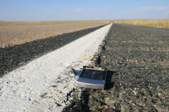 Broken cell phone on road. Broken run over cell phone on the road with selective focus stock photo