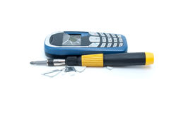 Broken cellular phone and screwdriver Royalty Free Stock Images