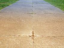 Broken cement walkway. Broken cement sidewalk with grass Royalty Free Stock Photography
