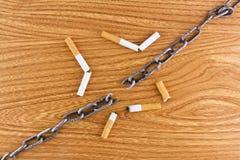 broken chain cigaretter över texturträ Royaltyfria Foton