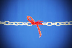 Broken chain connected with red threads. Broken chain connected with a red threads stock photography