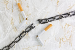 Broken chain over marble texture and cigarettes Royalty Free Stock Photos