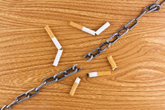 Broken chain over wood texture and cigarettes. Broken chain and cigarettes over wood texture background stop smoking concept Royalty Free Stock Photos