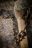 Broken Chains. Pillar holding at one side the broken chains, that are laying on the ground. Metaphoric staying for free yourself from the ballast that surrounds Royalty Free Stock Image
