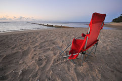 Broken chair on beach by ocean during sunrise Stock Images