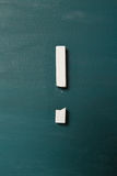 Broken chalk as exclamation point on green chalkboard Royalty Free Stock Images