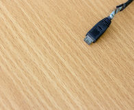 Broken charger cable on the wooden table. Close up image of broken charger cable on the wooden table Royalty Free Stock Image