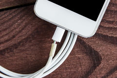 Broken Charging Cable With Phone  On A Wooden Background.  Stock Photo