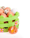 Broken chicken egg lies near a decorative basket of eggs Royalty Free Stock Images