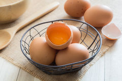 Broken chicken eggs. In basket on wooden background Stock Photos