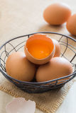 Broken chicken eggs in basket. On wooden background Royalty Free Stock Photos