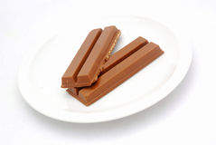 Broken chocolate bar. Two pieces of a delicious sweet brown broken chocolate bar on a plate. Image isolated on white studio background Royalty Free Stock Images