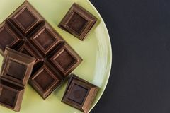 Broken chocolate bar. Broken dark chocolate bar slice in green plate Stock Images