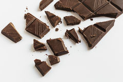 Broken chocolate bar, diagonal composition, white background, top view Stock Images