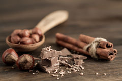 Broken chocolate bar, hazelnut and cinnamon on wooden background Royalty Free Stock Image