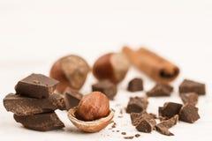 Broken chocolate bar, hazelnut and cinnamon on wooden background Royalty Free Stock Image
