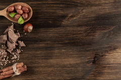 Broken chocolate bar, hazelnut and cinnamon on wooden background Stock Photos