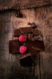 Broken chocolate bar with red ripe  raspberries on dark brown  b Royalty Free Stock Photography
