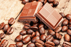 Broken chocolate bar and spices. On wooden table stock image