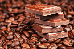 Broken chocolate bar and spices. On wooden table Royalty Free Stock Photos