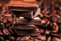 Broken chocolate bar and spices. On wooden table royalty free stock image