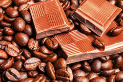 Broken chocolate bar and spices. On wooden table Royalty Free Stock Photo
