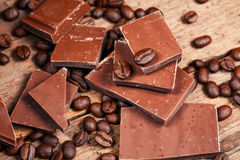 Broken chocolate bar and spices. On wooden table royalty free stock photography