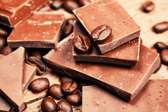 Broken chocolate bar and spices. On wooden table stock images