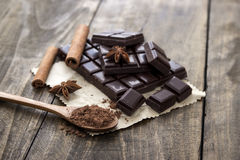 Broken chocolate bar and spices on wooden table. Royalty Free Stock Photo