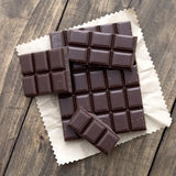 Broken chocolate bar  on wooden table. From above Royalty Free Stock Photography
