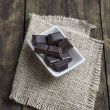 Broken chocolate bar on wooden table Royalty Free Stock Image