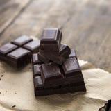 Broken chocolate bar  on wooden table. Stock Photos
