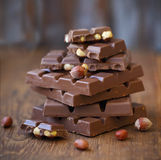 Broken chocolate bars and hazelnuts (filbert) on wooden table Stock Images
