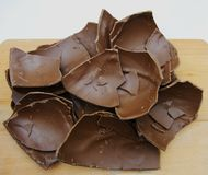 Broken chocolate Easter egg on a wooden table royalty free stock images